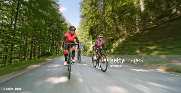 drie vrouwen rijden racefietsen op bergweg - wielrennen stockfoto's en -beelden