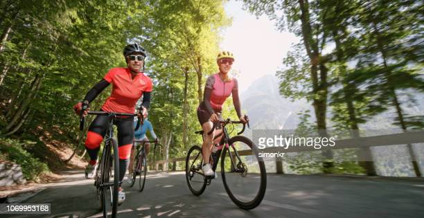 three women riding road bikes on mountain road - road cycling stock pictures, royalty-free photos & images