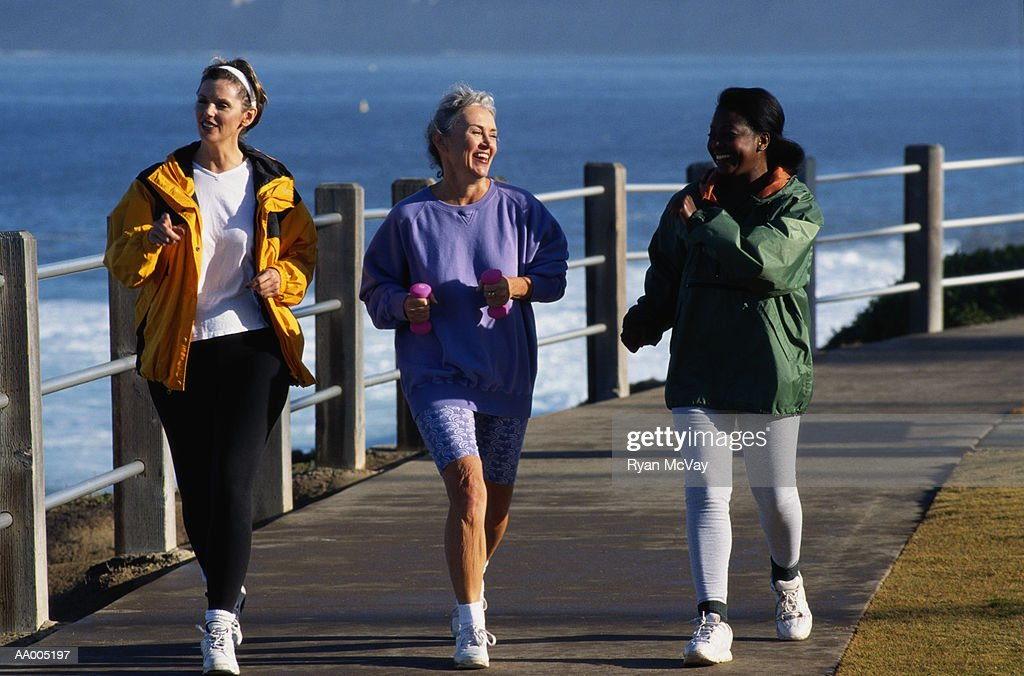 Three Women Running on a Path by a Bay : Stock Photo