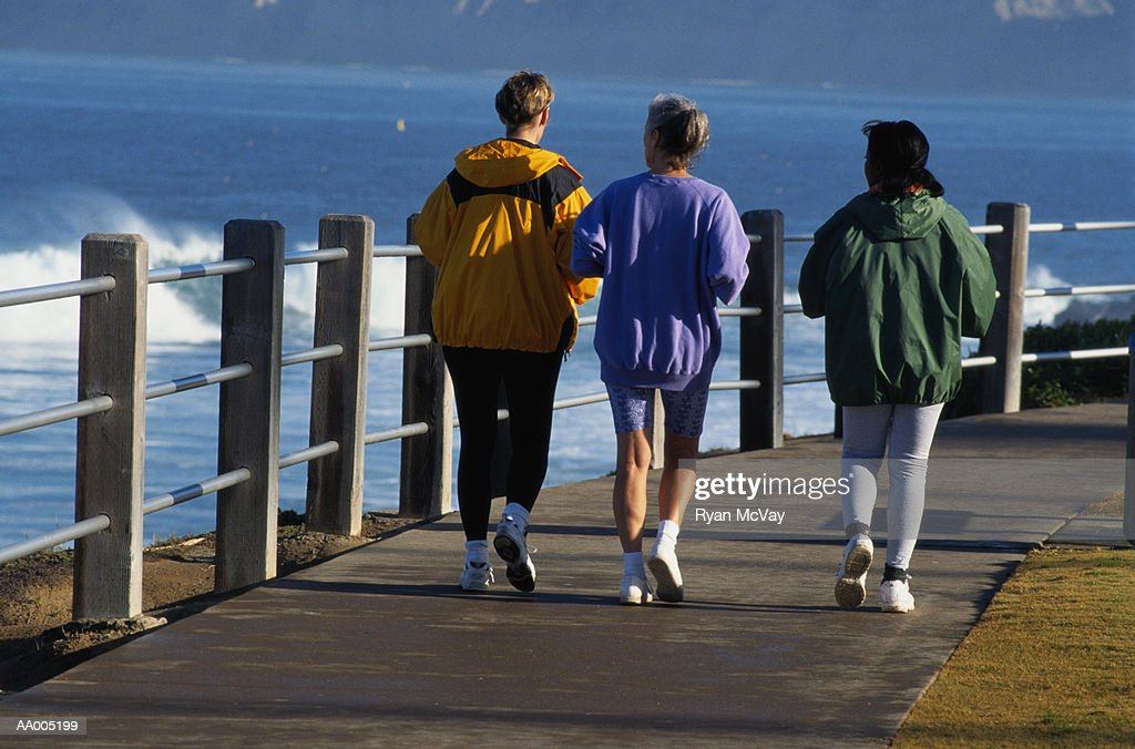 Three Women Running on a Path by the Ocean : Stock Photo