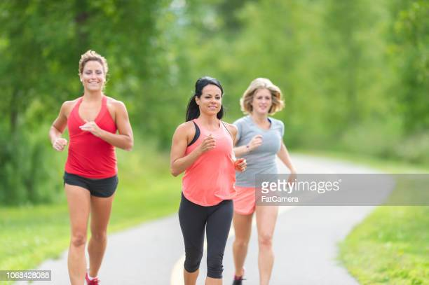 three women running outside - participant stock pictures, royalty-free photos & images