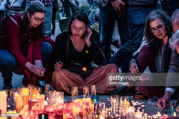 Three women seen lighting candles in the center of the Catalunya Square in memory of the 1050 days in prison of the Catalan political prisoners A...