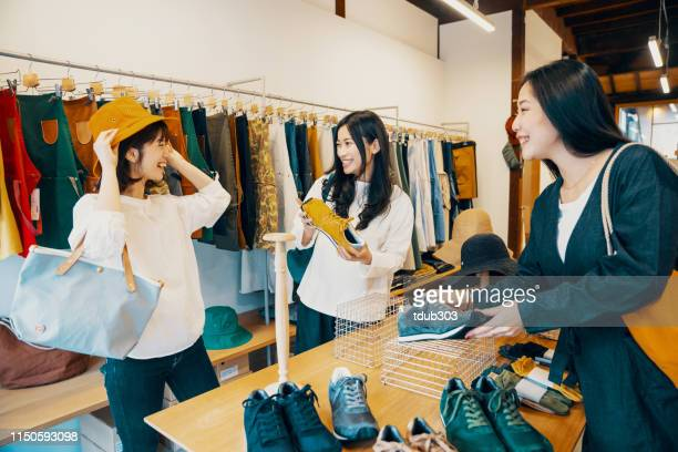 three women shopping together in a clothing store - merchandise stock pictures, royalty-free photos & images