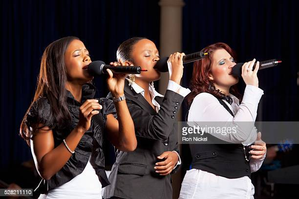 Three Women Singing Into Microphones