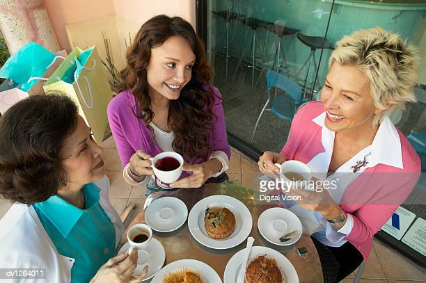 Three Women Sit at a Table on a Patio Having a Coffee Break and a Snack