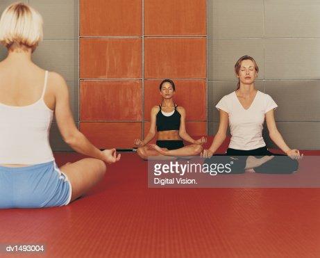 three women sit meditating in the lotus position yoga