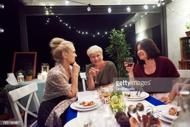 Three women sitting at dinner table, drinking from wine glasses