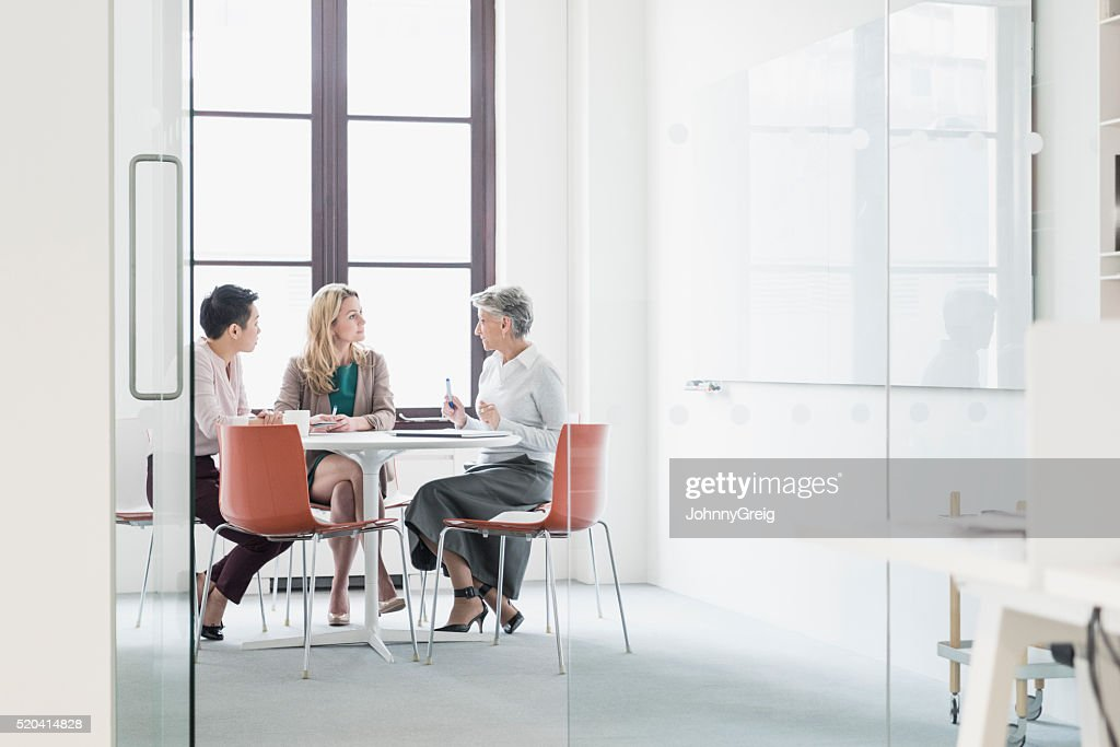 Three women sitting at table in modern office : Stock Photo
