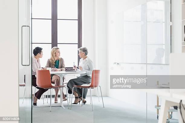 three women sitting at table in modern office - bedrijven financiën en industrie stockfoto's en -beelden