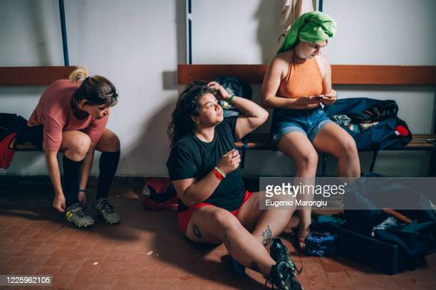 three women sitting in the changing room after rugby training. - cleats stock pictures, royalty-free photos & images