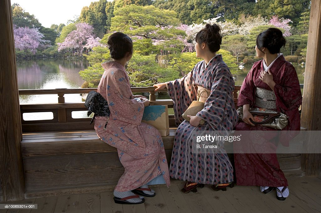 Three women sitting on bench in wooden covered bridge : Foto stock