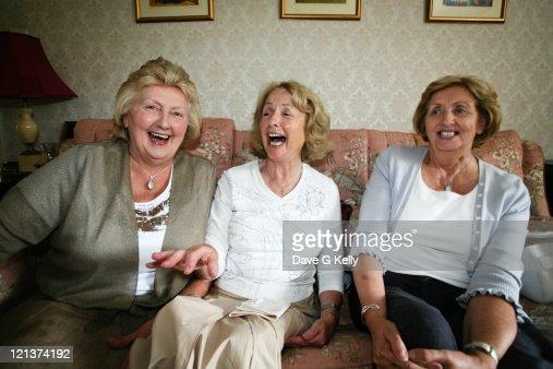 Three women sitting on couch sharing joke