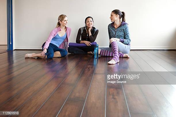 Three women sitting on gym floor