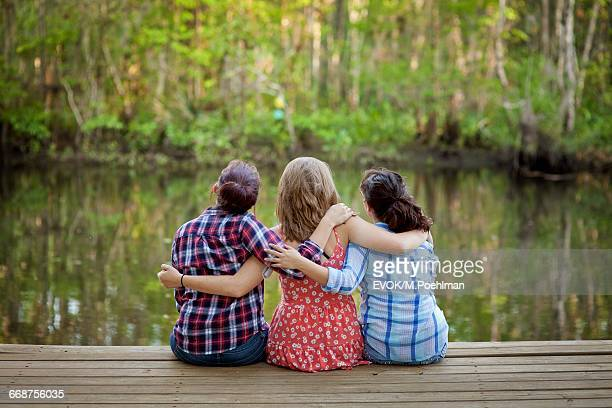 Three women sitting on pier