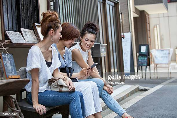 Three women sitting outdoors, looking at cellphone.