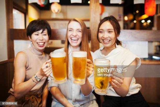 three women sitting side by side at a table in a restaurant, holding large glasses with beer. - 乾杯 ストックフォトと画像
