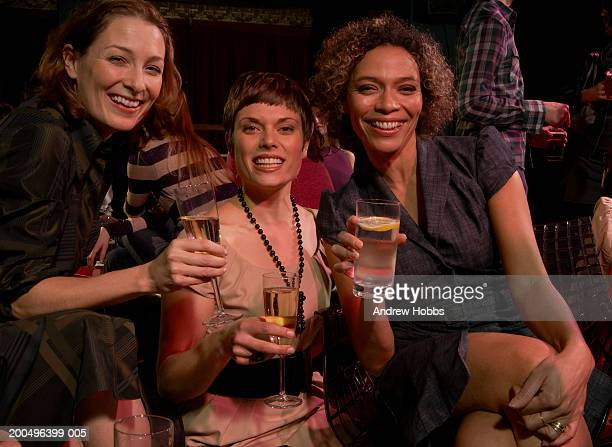 Three women sitting with drinks at table in club, smiling, portrait
