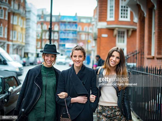 three women smiling and walking on the street - jcbonassin fotografías e imágenes de stock