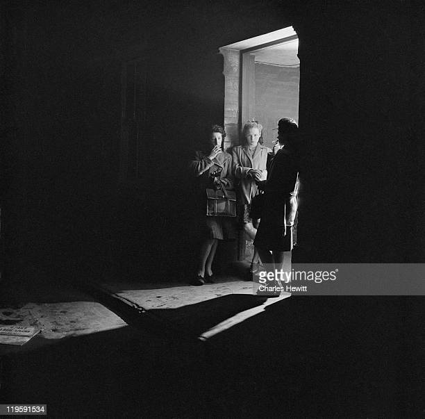 Three women smoking in a doorway on Christmas Street formerly Noel Street in the south London borough of Southwark December 1946 Picture Post 4277...