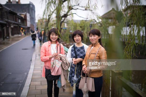 Three women standing nearby river in Japanese historical place