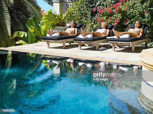 Trois femmes bronzage sur les chaises longues au bord de la piscine