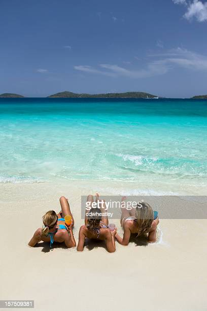 three women sunbathing on the beach