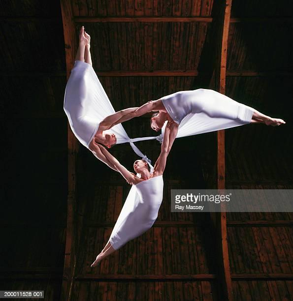 three women suspended from ceiling linking arms, view from below - artist stock-fotos und bilder