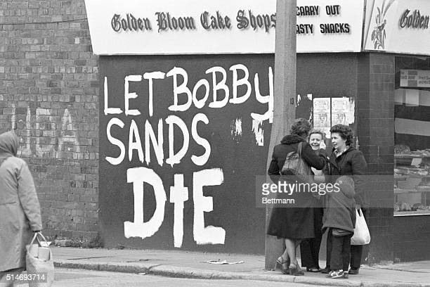 Three women talk casually near a graffitied message directed toward hunger striker Bobby Sands well in to his protest against British forces in...