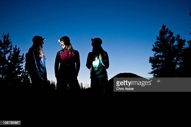 Three women talk while enjoying a twilight hike illuminated by headlamp.