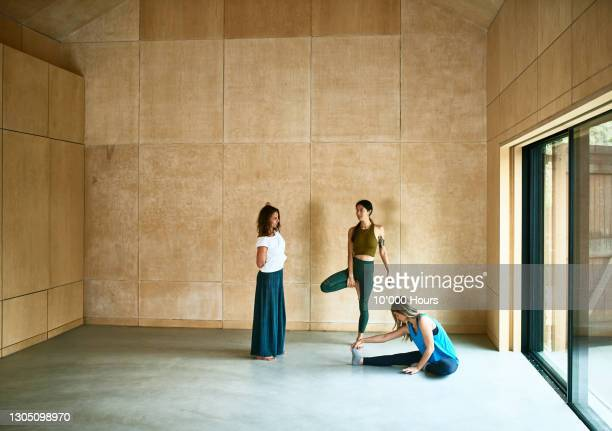 three women talking in yoga studio - healthy lifestyle stock pictures, royalty-free photos & images