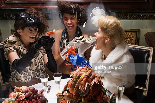 Three women tearing apart lobster