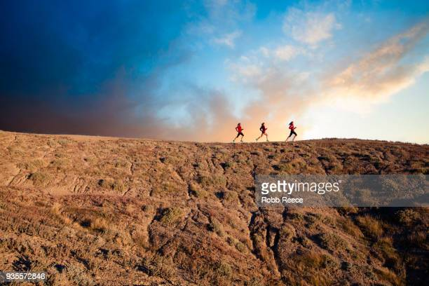 three women trail running in the desert at sunrise - robb reece stock-fotos und bilder