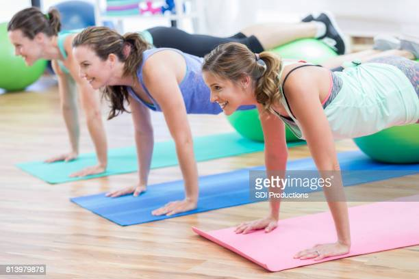 three women use exercise balls during pushups at the gym - floor gymnastics stock pictures, royalty-free photos & images