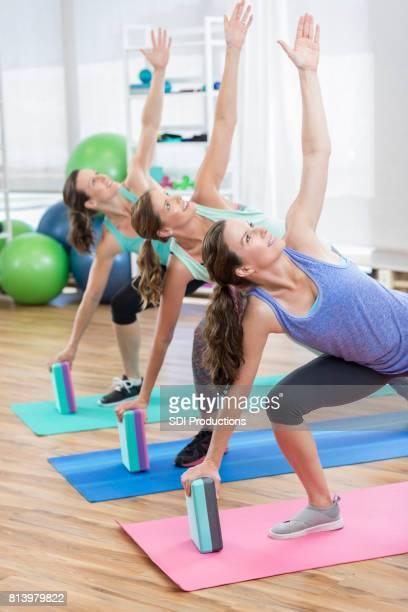 Trois femmes utilisent des blocs d'exercice pour se fend au gymnase