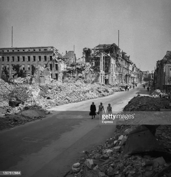 Three women walk along bombed damaged streets and buildings showing the destruction of the city in July 1945 following the allied occupation of...