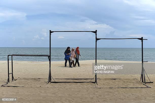 Three women walk on Teluk Cempedak beach on the outskirts of Kuantan peninsular Malaysia's northeastern Pahang state on November 22 2016 / AFP / MOHD...