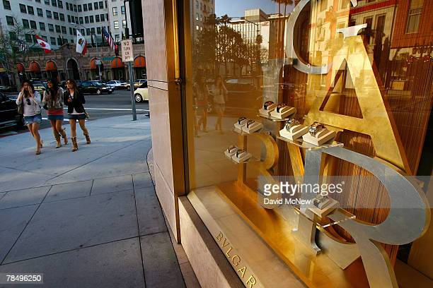 Three women walk past businesses that cater to high-end luxury item consumers along Rodeo Drive on December 14, 2007 in Beverly Hills, California. In...