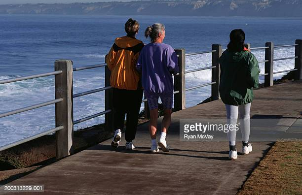 Three women walking along pier, rear view