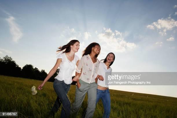 Three women walking arm in arm through meadow