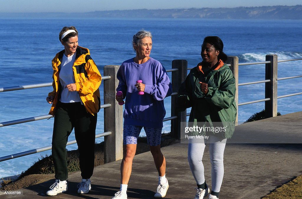 Three Women Walking Beside the Ocean : Stock Photo