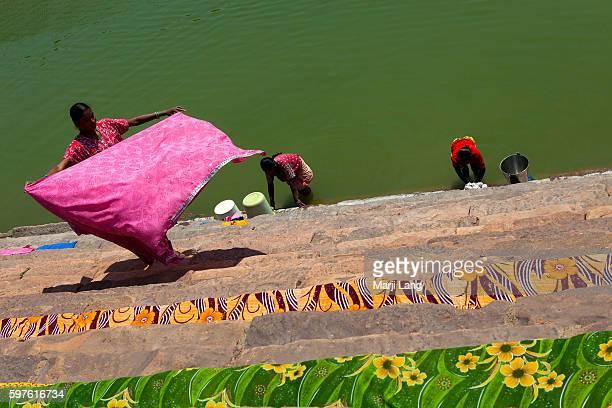Three women washing and drying saris at Badami lake