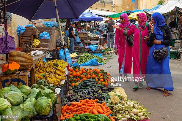 Three women wearing djellaba at market in Fez Morocco