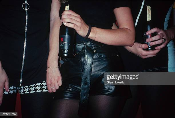 Three women wearing hot pants and holding bottles of cider at a night club London 1991