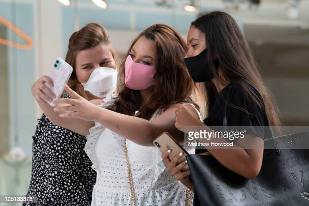 Three women wearing protective face masks take a selfie on Queen Street as non-essential shops open for the first time since the start of lockdown on...