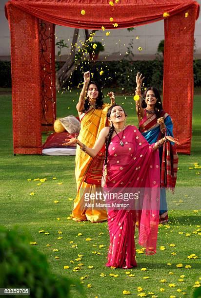 three women wearing saris in front of tent