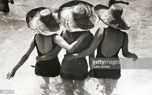 Three women wearing sunhats in pool, rear view (B&W)