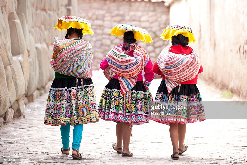 Three women wearing traditional clothes passing the last remaining Inca wall in Cusco. Peru. : Stock Photo