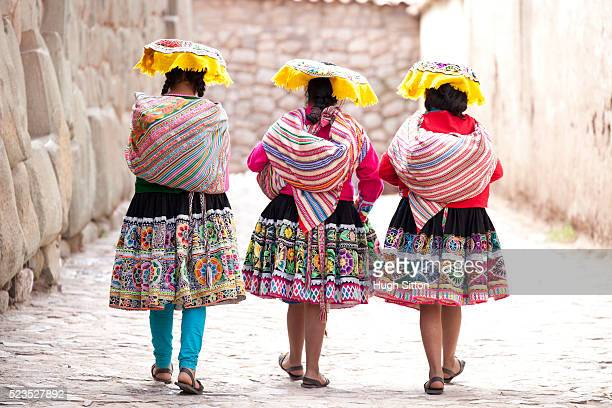 Three women wearing traditional clothes passing the last remaining Inca wall in Cusco. Peru.