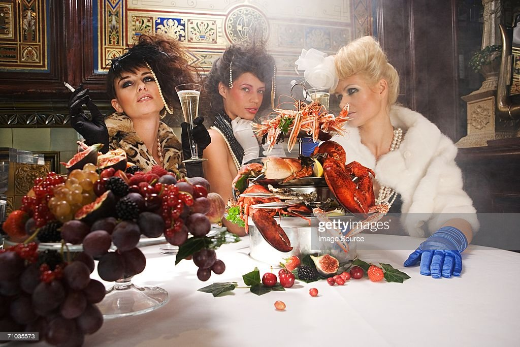 Three women with a feast of seafood and fruit : Stock Photo