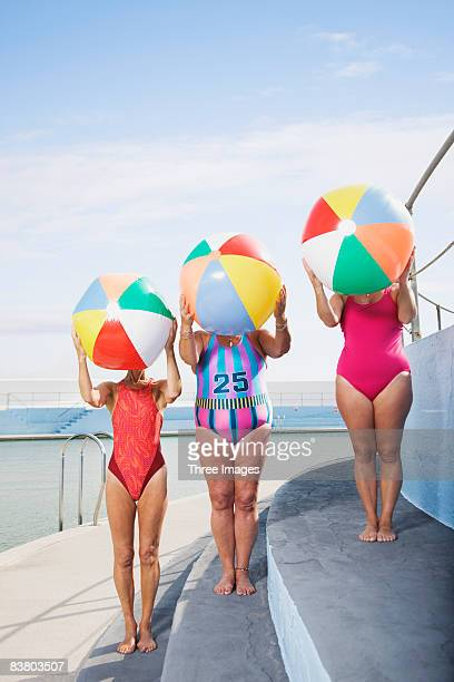 three women with beach balls at pool - badkleding stockfoto's en -beelden